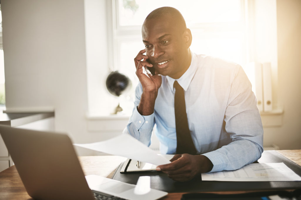 Smiling young African business professional talking to a client on his cellphone while sitting at his desk in an office